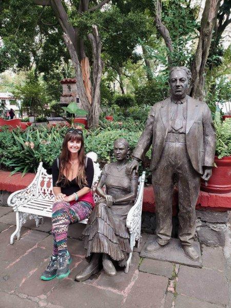 mulher (eu) sentada com as estátuas em tamanho original de Frida Kahlo e Diego Rivera