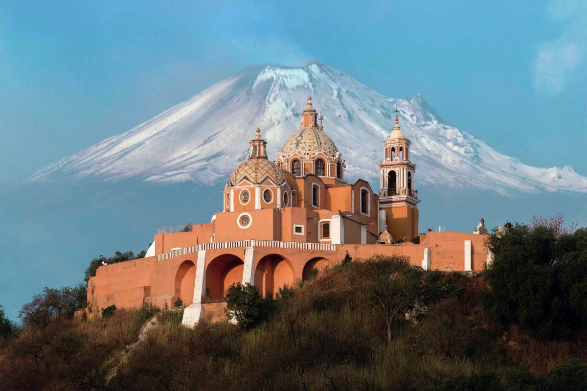 igreja amarela no topo da montanha com vulcão de fundo com neve no topo