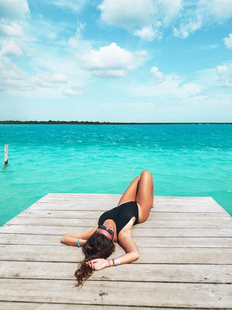 deitada no deck em frente a lagoa bacalar