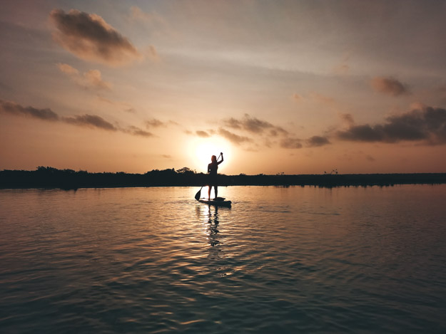 andando de stand up paddle com o nascer do sol de fundo Bacalar