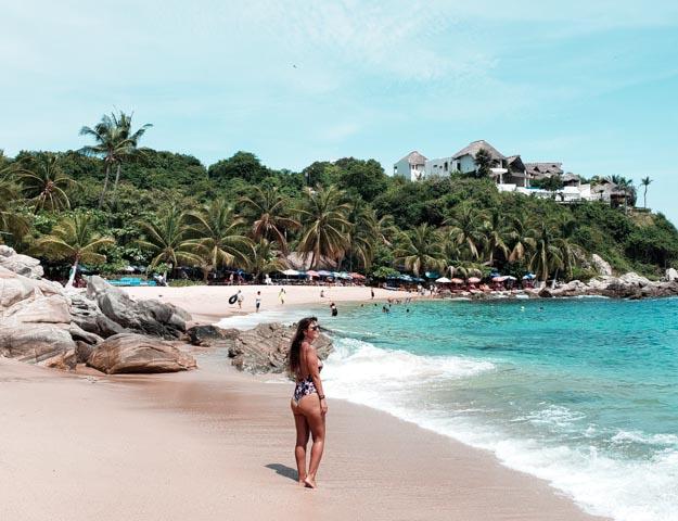 eu em pé na areia com a playa manzanillo de fundo