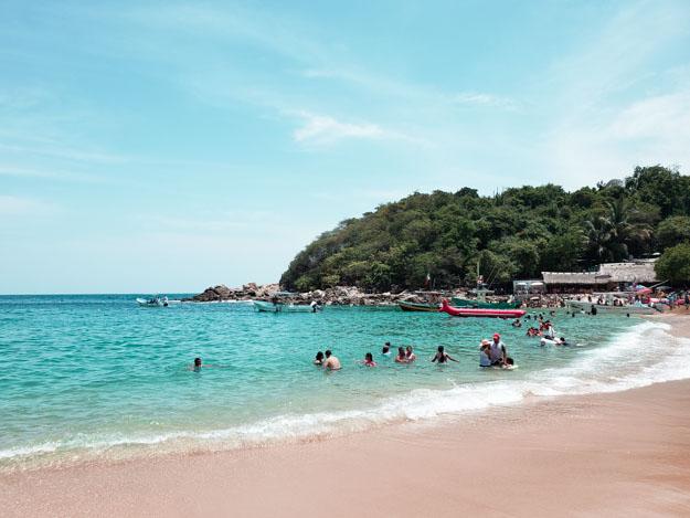 pequena praia de puerto angelito com algumas pessoas nadando